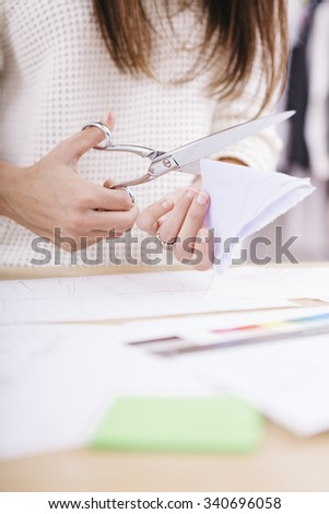 Young designer with scissors is cutting the designer clothes - stock photo