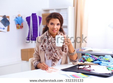 Young designer woman sitting on the desk with cup
