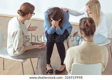 Young despair woman crying during group therapy - stock photo