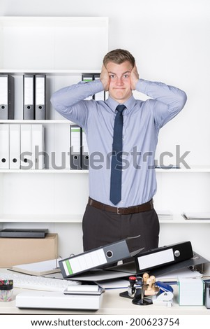 Young despaired businessman is standing in front of many files on his desk in the office. A shelf is in the background. The man is looking to the camera. - stock photo