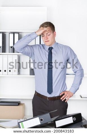 Young despaired businessman is standing in front of many files on his desk in the office. He holds one hand at his head. A shelf is in the background. The man is looking to the files.