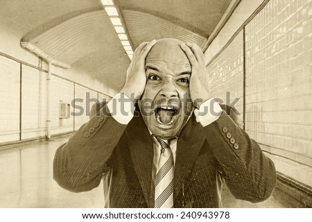 Young desperate businessman fired from job screaming in stress wearing suit and tie on street subway tunnel suffering and looking destroyed with hands on his head in crisis - stock photo