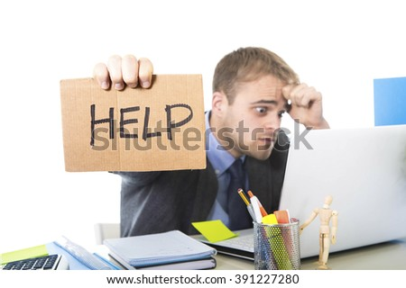 young desperate businessman holding help sign looking worried suffering work stress sitting at computer desk on white background office in business project problem - stock photo