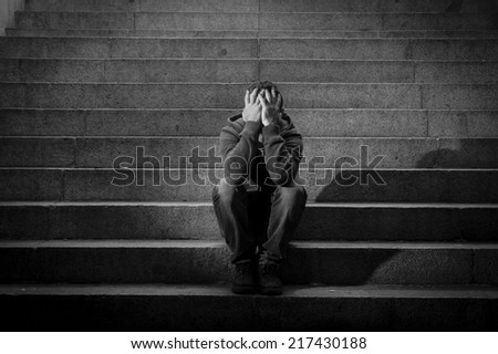 Young desperate man in casual clothes abandoned lost in depression sitting on ground street concrete stairs alone suffering emotional pain, sadness, looking sick in grunge lighting - stock photo
