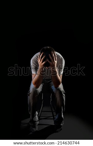 young desperate man suffering and covering face with hands in deep depression, pain, emotional disorder, grief and desperation concept isolated on black background in edgy and grunge studio lighting  - stock photo