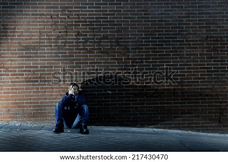 Young desperate man who lost job abandoned and lost in depression sitting on ground street corner against brick wall suffering emotional pain, crying alone in grunge lighting - stock photo