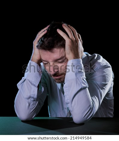 young desperate sick businessman suffering headache with hands on head in deep depression, pain , emotional disorder, grief and desperation concept isolated on black background - stock photo