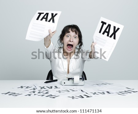 Young desperate woman at her desk showing terrible tax bills to the camera while shouting out - stock photo