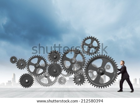 Young determined businessman making gear mechanism move - stock photo