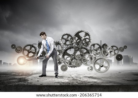 Young determined businessman with wrench fixing mechanism