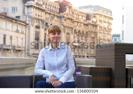 Young determined businesswoman sitting at table on office builing terrace