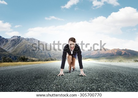 Young determined businesswoman standing in start position - stock photo