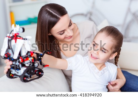Young development.  Cheerful delighted smiling little girl playing with robot while sitting on the couch with her caring mother  - stock photo