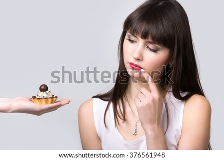 Young dieting beautiful woman sitting in front of delicious cream and chocolate tart cake, looking at it appraisingly, healthy lifestyle concept, studio, gray background, isolated, copy space - stock photo