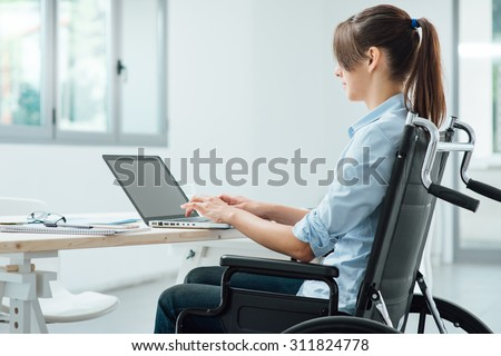 Young disabled business woman in wheelchair working at office desk and typing on a laptop, accessibility and independence concept - stock photo