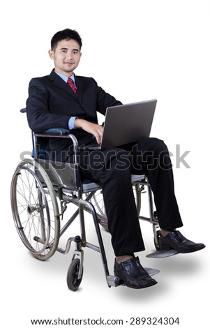 Young disabled businessman wearing formal suit and sitting on wheelchair while holding a laptop computer - stock photo