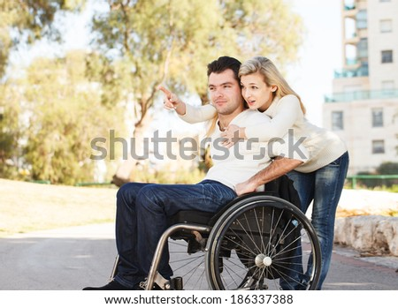 Young disabled man and his girlfriend - stock photo