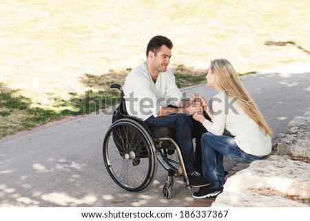 Young disabled man on a wheelchair talking with his girlfriend in the park