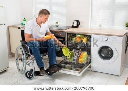 Young Disabled Man Sitting On Wheelchair Working In Kitchen - stock photo