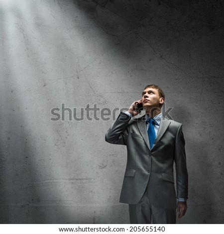 Young disappointed businessman talking on mobile phone with tears in eyes - stock photo
