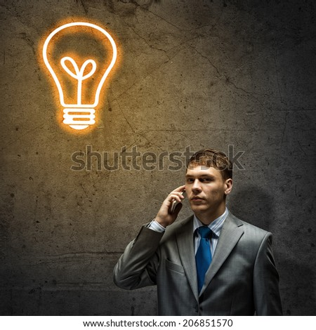 Young disappointed businessman talking on mobile phone with tears in eyes