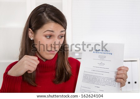 Young disappointed woman staring at business contract in german language - time work - stock photo