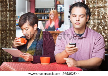 Young distracted African American couple using digital devices in cafe - stock photo