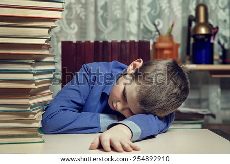 Young distressed student sleeping on the desk.