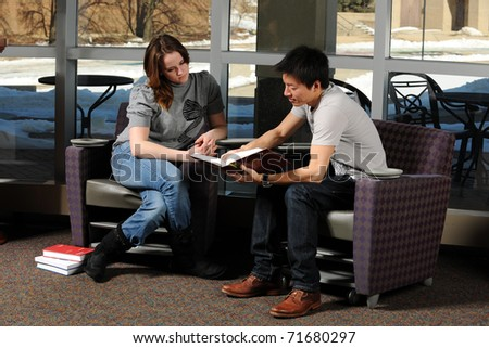 Young Diverse Students in College campus reading a book - stock photo