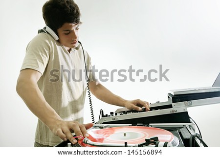 Young DJ playing and mixing music in a night club, with his headphones on isolated against a white background. - stock photo