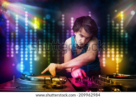 Young Dj playing songs in a disco with light show - stock photo