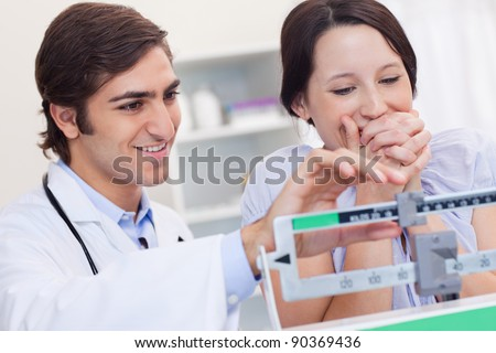 Young doctor adjusting scale for excited patient