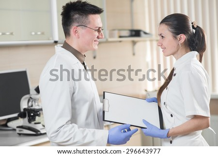 young doctor and assistant standing and holding folder tablet in the laboratory