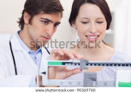 Young doctor and patient adjusting the scale - stock photo