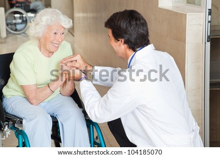 Young doctor comforting happy senior woman in hospital - stock photo