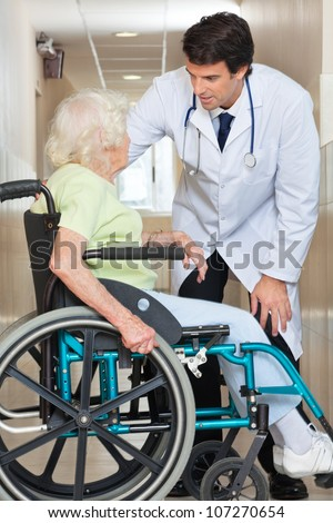 Young doctor communicating with senior female patient sitting in wheelchair at hospital