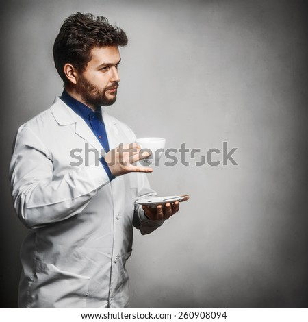 Young doctor drink tea coffee cheerio Grey background - stock photo