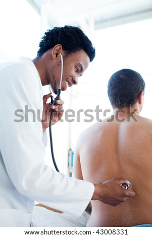 Young doctor examining a patient sitting on a hospital bed - stock photo