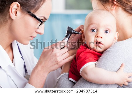 Young doctor examining baby boy with otoscope - stock photo