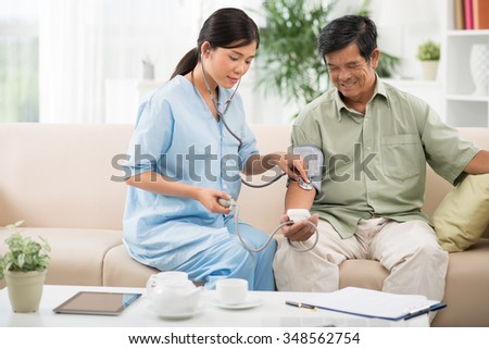 Young doctor helping senior man to check blood pressure at home