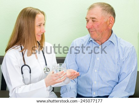Young doctor helping the elderly man to take the pills
