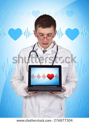 young doctor holding laptop with pulse symbol on screen - stock photo