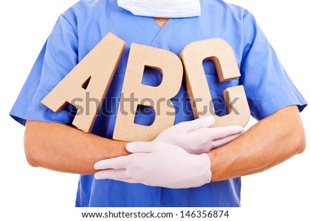 Young doctor holding letters a b c - stock photo