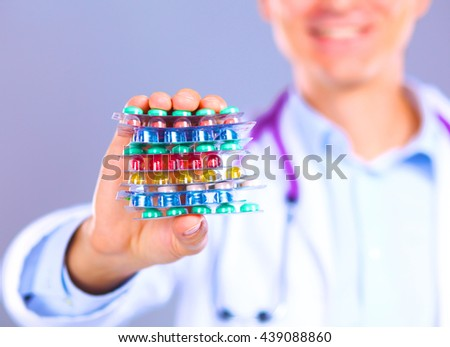young doctor holding pills in his outstretched hand packaging - stock photo