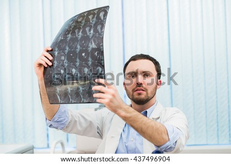 Young doctor holding x-ray mri scan and looking worried - stock photo