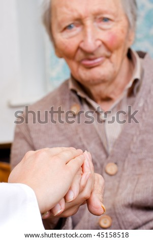 Young doctor holds old man's hand - stock photo