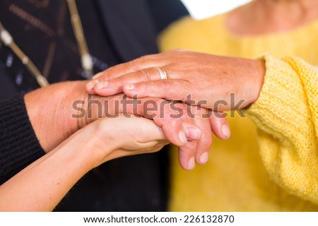 Young doctor holds the old women hands