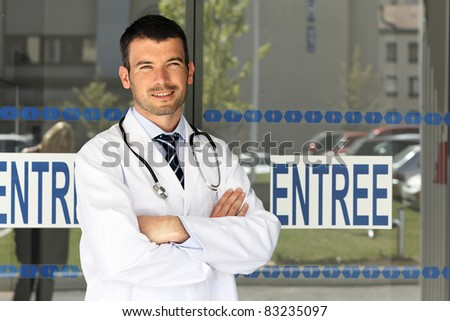 young doctor in front of hospital entry - stock photo
