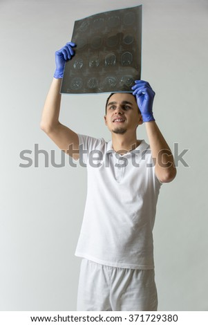 Young doctor in white uniform and blue latex gloves holds a tomography results in his hands. He looks at the tomography results. Studio photo on a gray background. Vertical. - stock photo