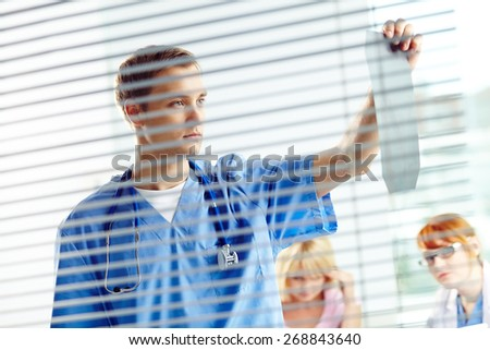 Young doctor looking at x-ray in office - stock photo
